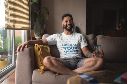 T Shirt Mockup of a Smiling Man with an Arm Tattoo Relaxing at Home 21345