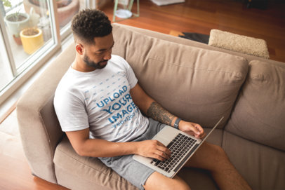 T-Shirt Mockup of a Man with an Arm Tattoo Using his Laptop at Home 21346