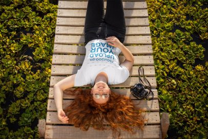 Mockup of a Red-Haired Girl Wearing a T-Shirt while Resting on a Wooden Bridge 21940