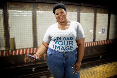 Plus Size T-Shirt Mockup Featuring a Happy Woman with her Phone at a NYC Subway Station 22586