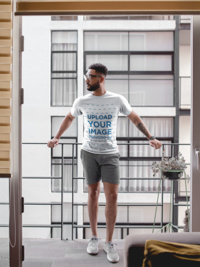 T-Shirt Mockup of a Man Standing on His Balcony 21336