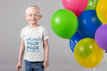 Round Neck Tee Mockup of a Smiling Kid with Glasses Standing Next to a Set of Balloons 22057
