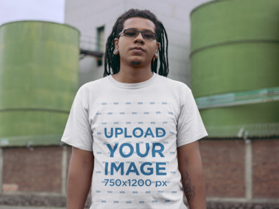 T-Shirt Mockup of a Serious Man With Dreads In Front of an Industrial Site 22058