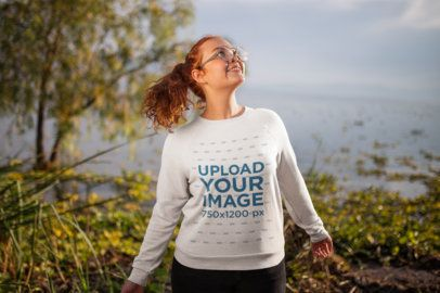 Mockup Featuring a Smiling Girl Wearing a Crewneck Sweater by a Lake 21942