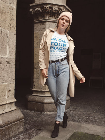 Mockup of a Girl Wearing a T-Shirt and a Trench Coat Outside a Stone Church 22655