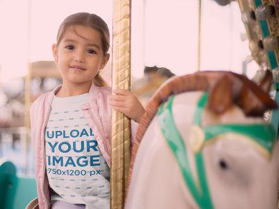 Mockup of a Little Girl Riding a Carousel Horse Wearing a Tshirt and a Pink Jacket 22527
