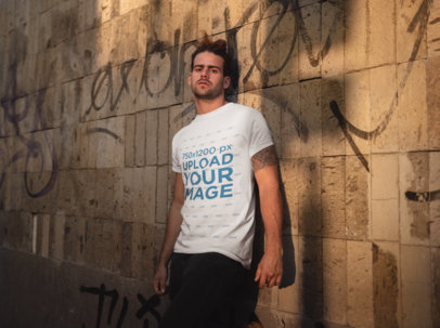 T-Shirt Mockup of a Man Leaning on a Graffiti Painted Wall 19946