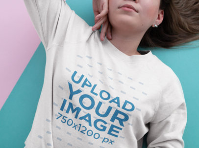 Closeup Mockup Showing a Woman Wearing a Crewneck Sweater Lying on a Bicolor Surface 18415