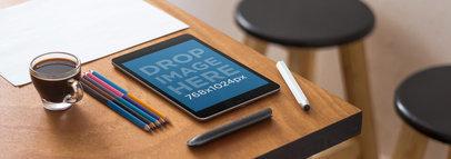 Tablet Mockup of a Black iPad Mini Over a Designer Studio