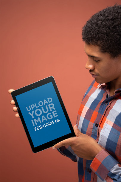 Mockup of a Man Holding a Space Gray iPad in Portrait Position 22633