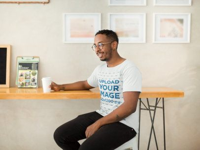 Round Neck Tee Mockup with a Smiling Man Sitting at a Café 21038