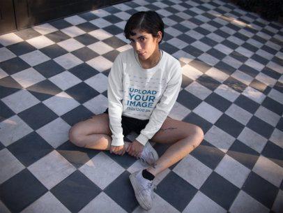 Sweatshirt Mockup of a Woman Sitting Cross Legged on a Checkered Floor 18280