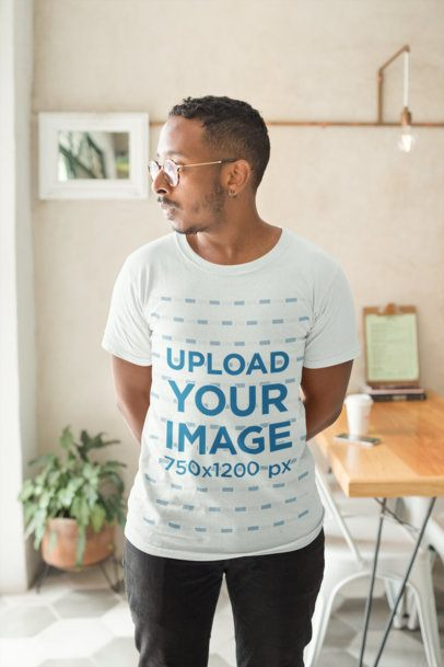 Mockup of a Man Wearing a T-Shirt in His Apartment Looking Towards His Window 21044
