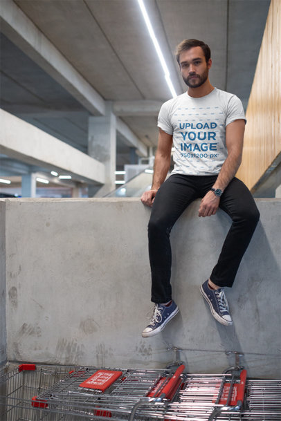 T-Shirt Mockup of a Man Sitting on a Cement Wall 20053