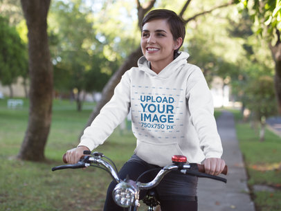 Hoodie Mockup Featuring a Happy Girl Riding a Bicycle in the Park 17925
