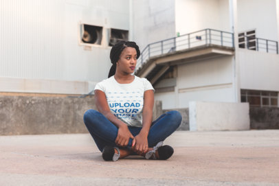T-Shirt Mockup Featuring a Girl with Braids Sitting Outside a Warehouse 18178