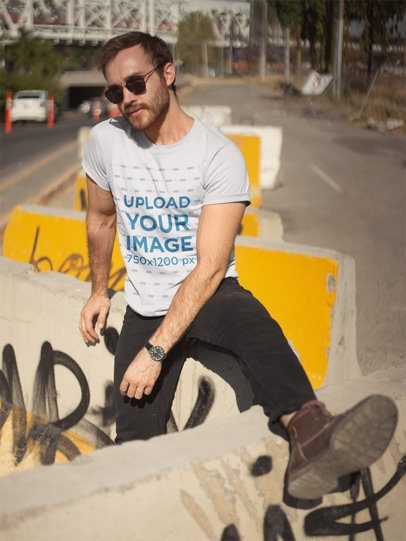 T-Shirt Mockup of a Man Sitting on a Concrete Barrier 20058