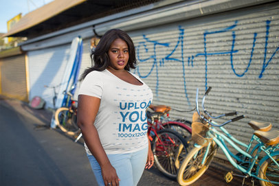 Plus Size T-Shirt Mockup Featuring a Woman Standing in Front of Bicycles  18302