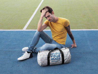 Mockup of a Man Sitting Next to a Duffle Bag at a Tennis Court 23221