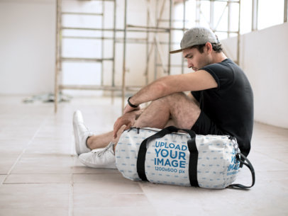 Mockup of a Man Sitting Pensively Next to a Gym Bag 23059