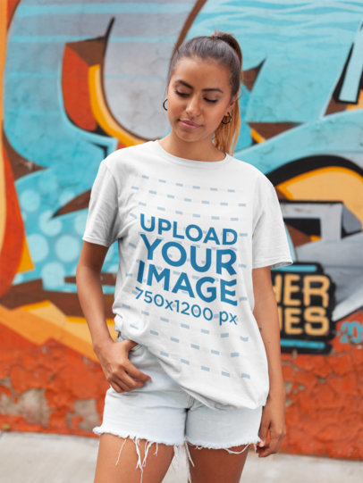 Mockup of a Woman Wearing a Unisex T-Shirt in Front of Graffiti 22788