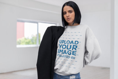 Sweater Mockup of a Girl Holding a Black Coat in a White Room 23117
