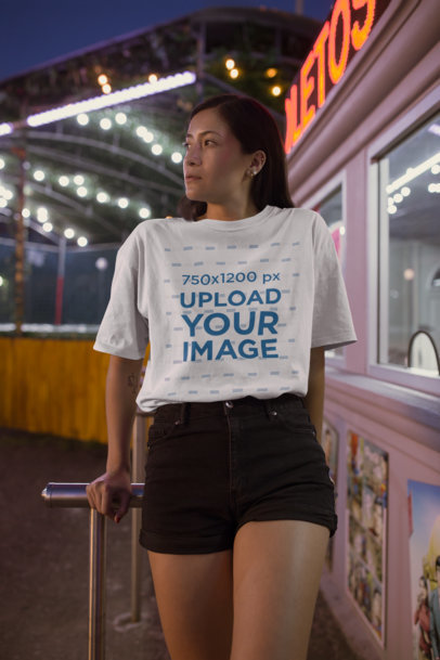 Mockup of a Woman Wearing a Unisex T-Shirt at a Fair Admission Box 22974