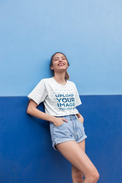 Mockup of a Smiling Girl Wearing a Round Neck Tee Leaning Against a Wall 22956