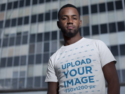 Mockup of a Cool Man Wearing a Tee in Front of a Skyscraper 22772