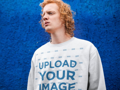 Crewneck Sweatshirt Mockup of a Red-Haired Man Against a Blue Wall 21192