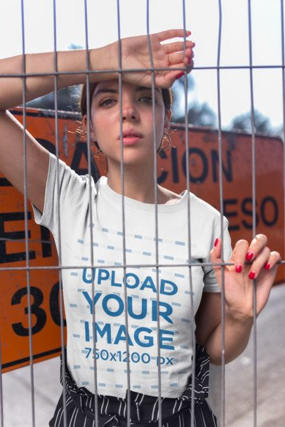 Mockup of a Trendy Woman Wearing a Tee Behind a Fence 20699
