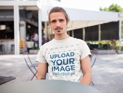 T-Shirt Mockup of a Smiling Man Sitting at a Table Outside 20156