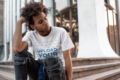 Tee Mockup Featuring a Man with Afro Wearing Distressed Jeans in Front of a City Building 18073