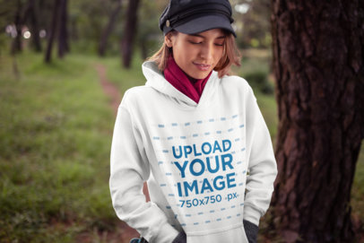 Mockup of a Beautiful Young Woman Wearing a Hoodie and a Trendy Kepi Hat 23273