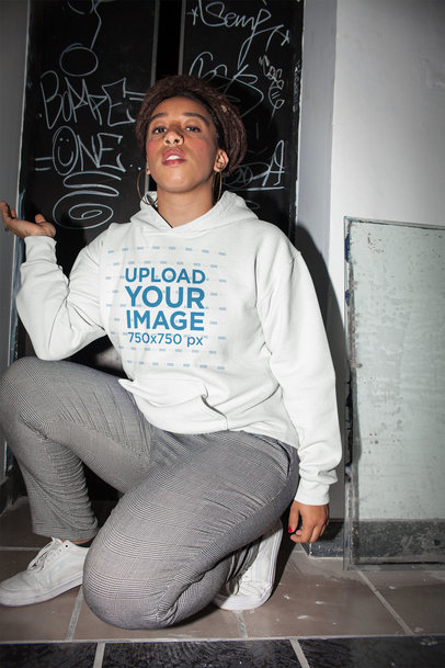 Pullover Hoodie Mockup of a Kneeling Woman with Locks in Flash Photography 23426