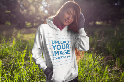 Hoodie Mockup of a Young Woman Standing in a Meadow 23274