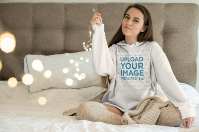 Hoodie Mockup of a Beautiful Young Woman Holding Twinkle Lights Sitting on a Bed 23213