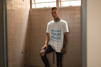 T-Shirt Mockup of a Punk Man with Tattoos Leaning Against a Tiles Wall 23461