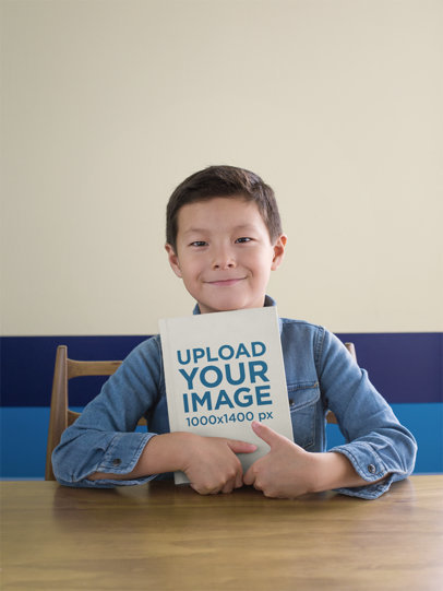 Book Mockup Featuring a Child Sitting on a Wooden Table 23721