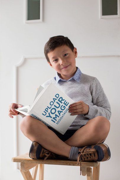 Mockup of a Young Boy Sitting With His Legs Crossed Reading a Book 23724