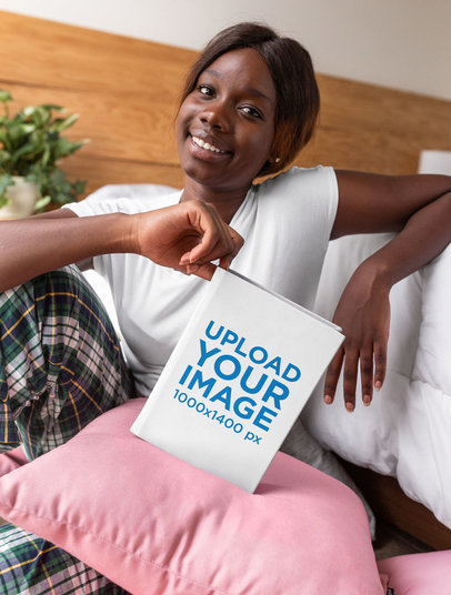 Mockup of a Smiling Woman Holding a Hard Cover Book Against a Pillow 23710