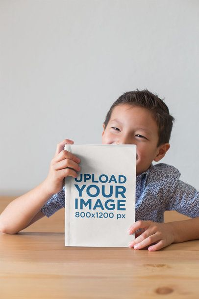 Book Mockup of a Little Boy Smiling and Showing off His Book 23725