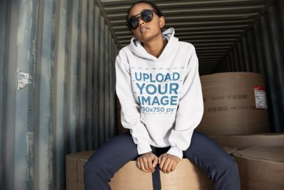 Mockup of a Cool Woman Wearing a Hoodie Sitting on Large Round Packages 24296