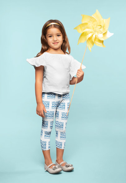 Mockup of a Little Girl Wearing Leggings Holding a Paper Windmill 23911
