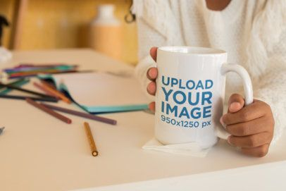 Mockup of a Mug Held by a Child Surrounded by Colored Pencils 24007