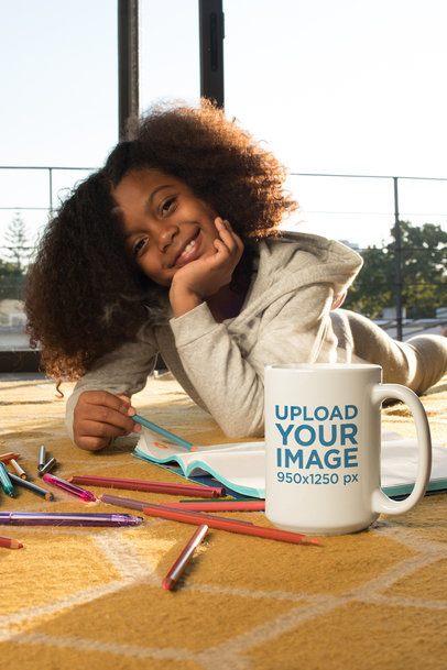 Coffee Mug Mockup of a Happy Girl Drawing While Lying on the Floor 24010