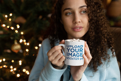 15 oz Mug Mockup of a Woman with Curly Hair Drinking Hot Cocoa in Front of a Christmas Tree 23500