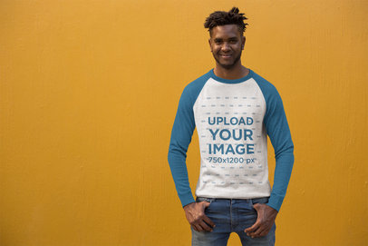 Mockup of a Trendy Man Wearing a Raglan Tee in Front of a Bright Wall 24113