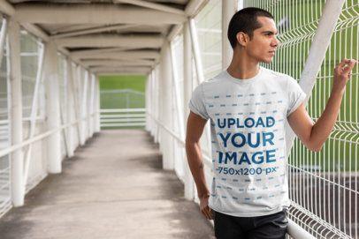 T-Shirt Mockup of a Man Standing on a Pedestrian Bridge 24530