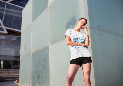 T-Shirt Mockup of a Woman with Short Hair and Leg Tattoos in a City Scenario 20177